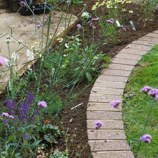 retrofit rain garden next to concrete driveway
